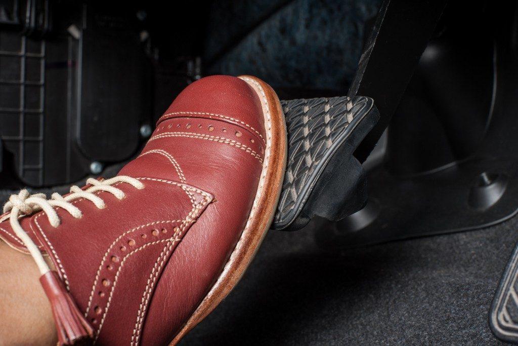 Foot pressing a break pedal