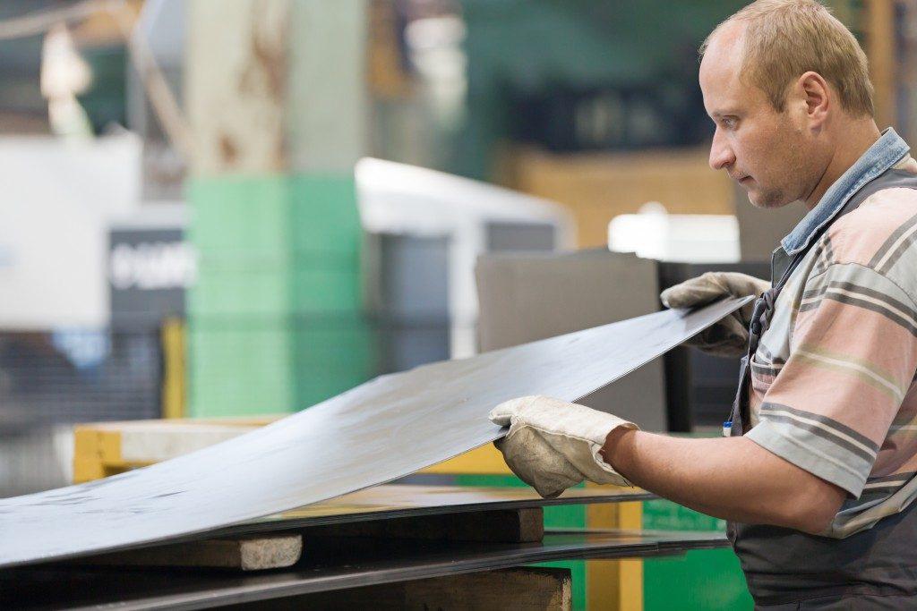 man holding a sheet of metal